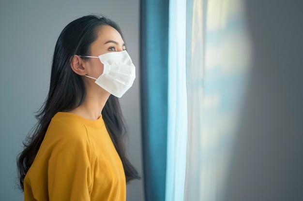 Eine junge schöne frau, die eine schützende gesichtsmaske trägt, die bereit ist, nach draußen zu gehen, gesundheitswesen und covid-19 konzept