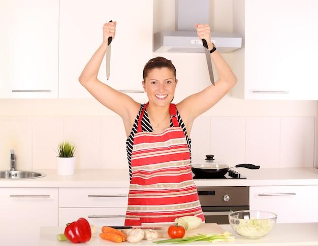 Eine junge schöne frau, die in einer modernen küche arbeitet