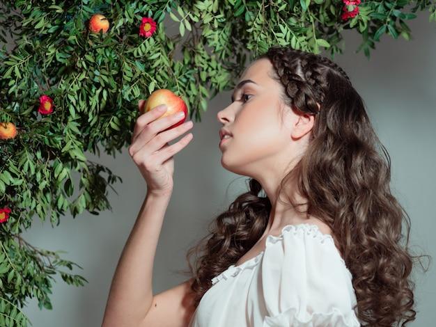 Eine junge schöne frau im garten eden schmeckt eine reife frucht