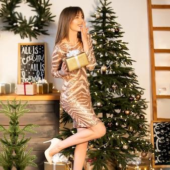 Eine junge schöne frau in einem glänzenden festlichen kleid steht in der nähe des neujahrsbaums und hält eine schachtel mit einem geschenk in den händen, die ihren lächelnden mund mit der hand bedeckt. weicher fokus.