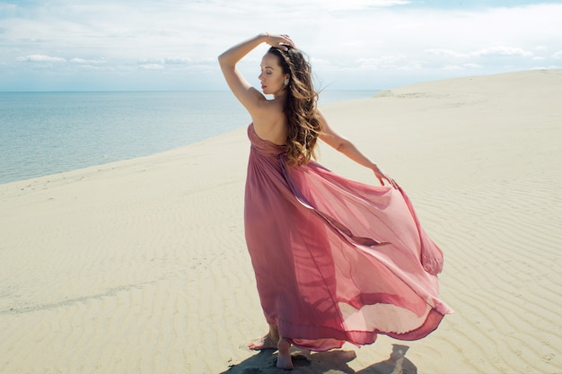 Eine junge schöne frau in einem rosa kleid geht auf den sanddünen