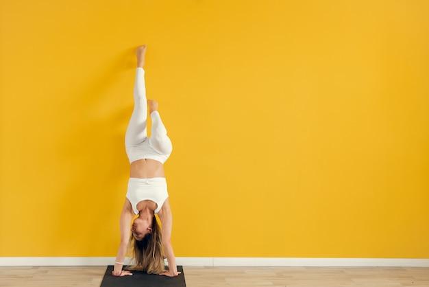Eine junge schöne frau in einer sportuniform führt eine schwierige yoga-asana durch und steht auf einer matte vor dem hintergrund einer gelben wand. ruhe, ausgeglichenheit und gesundes lebensstilkonzept. platz kopieren.