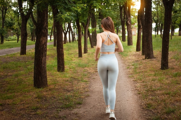 Eine junge schöne frau läuft bei sonnenuntergang im park. gesunder lebensstil, training im freien. training, fitness, gewichtsverlust