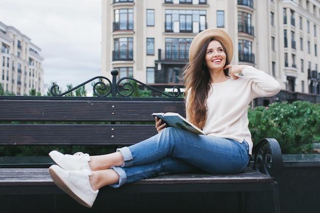 Eine junge schöne frau liest ein papierbuch.
