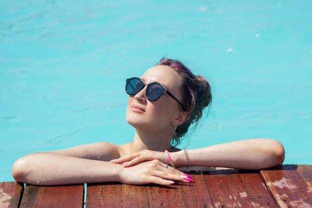Eine junge schöne frau mit schwarzer sonnenbrille entspannt sich am pool und schaut in die sonne?
