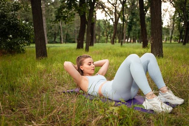 Eine junge schöne frau schüttelt die presse auf der gymnastikmatte im park auf dem rasen. training, outdoor, fitness. ausgebildeter muskulöser körper, gesunder lebensstil. aufladen