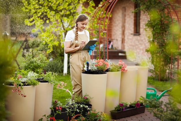Eine junge schöne gärtnerin hält eine tafel für notizen in der hand und überprüft den zustand der blumen.