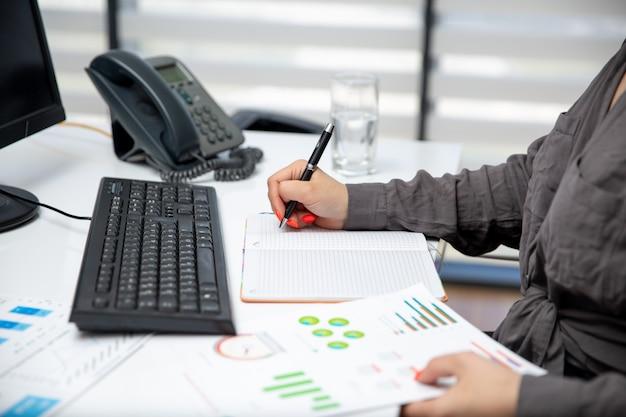 Eine junge schöne geschäftsfrau der vorderansicht, die an ihrem pc auf dem tisch zusammen mit telefon und grafiken arbeitet, notiert notizen jobaktivitäten technologie