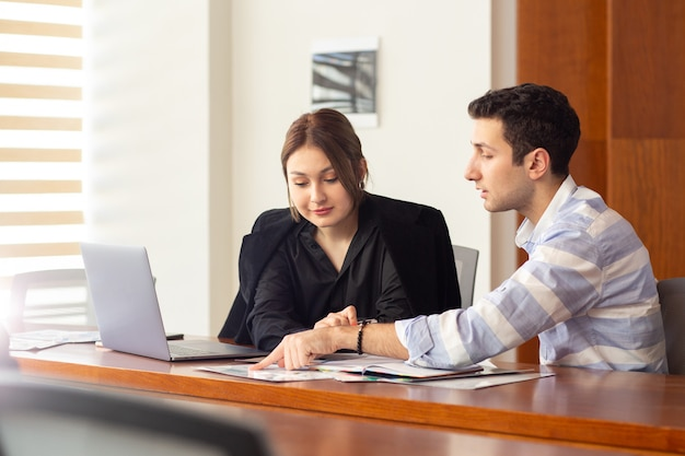 Eine junge schöne geschäftsfrau der vorderansicht in der schwarzen jacke des schwarzen hemdes zusammen mit dem jungen mann, der arbeitsprobleme in ihrem büroarbeitsjobgebäude bespricht