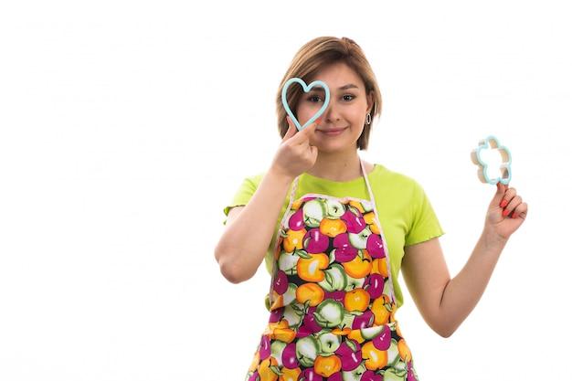 Eine junge schöne hausfrau der vorderansicht des bunten umhangs des grünen hemdes, der blaue figuren hält, die auf dem weißen hintergrundhausreinigungsküche lächeln