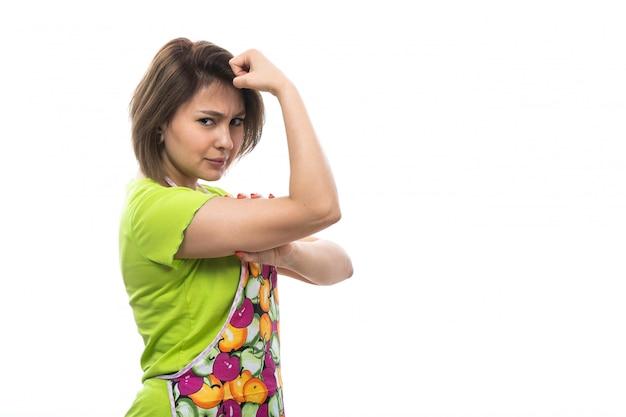 Eine junge schöne hausfrau der vorderansicht des bunten umhangs des grünen hemdes, der die weibliche küche des weißen hintergrundhauses beugt