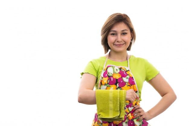 Eine junge schöne hausfrau der vorderansicht des bunten umhangs des grünen hemdes, der grünes handtuch hält, das auf der hausreinigungsküche des weißen hintergrundhauses lächelt