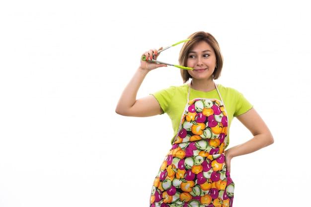 Eine junge schöne hausfrau der vorderansicht des bunten umhangs des grünen hemdes, der grünes küchengerät auf der weißen hintergrundhausreinigungsküche hält