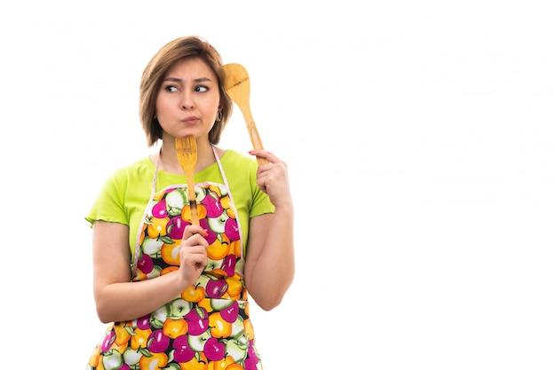 Eine junge schöne hausfrau der vorderansicht des bunten umhangs des grünen hemdes, der hölzernes küchengerät denkt, das auf dem weißen hintergrund hausreinigungsküche denkt