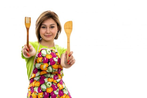 Eine junge schöne hausfrau der vorderansicht des bunten umhangs des grünen hemdes, der hölzernes küchengerät hält, das auf der weißen hintergrundhausreinigungsküche lächelt