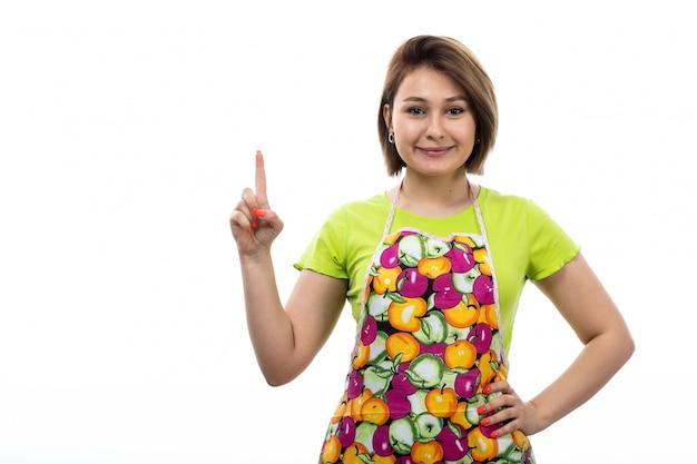 Eine junge schöne hausfrau der vorderansicht des bunten umhangs des grünen hemdes, der mit dem erhöhten finger lächelnd auf der weiblichen küche des weißen hintergrundhauses posiert