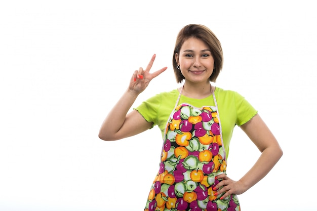 Eine junge schöne hausfrau der vorderansicht des bunten umhangs des grünen hemdes, der mit den erhabenen fingern posiert, die auf der weiblichen küche des weißen hintergrundhauses lächeln