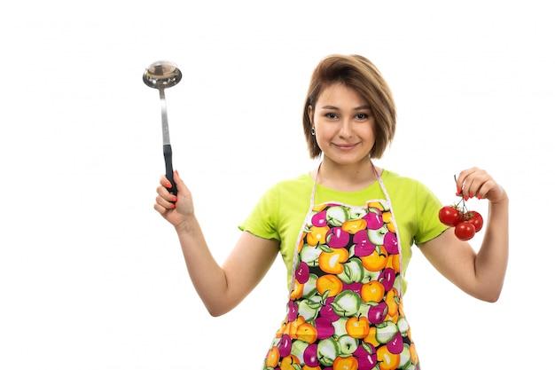 Eine junge schöne hausfrau der vorderansicht des bunten umhangs des grünen hemdes, der rote tomaten und den silbernen löffel hält, der auf der weiblichen küche des weißen hintergrundhauses lächelt