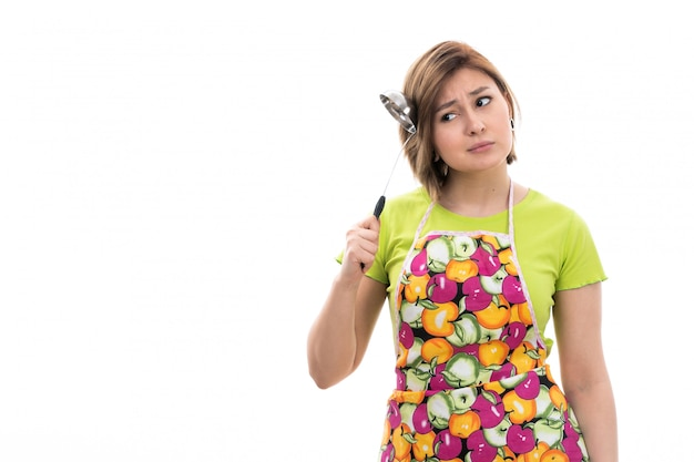 Eine junge schöne hausfrau der vorderansicht des bunten umhangs des grünen hemdes lächelnd, das küchengerät hält, das auf der weißen hintergrundhausreinigungsküche denkt