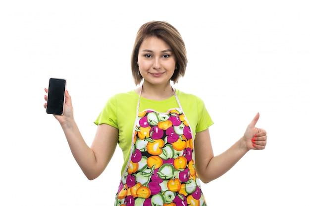 Eine junge schöne hausfrau der vorderansicht im bunten umhang des grünen hemdes, das das schwarze telefon zeigt, das glücklich auf der weiblichen küche des weißen hintergrundhauses lächelt