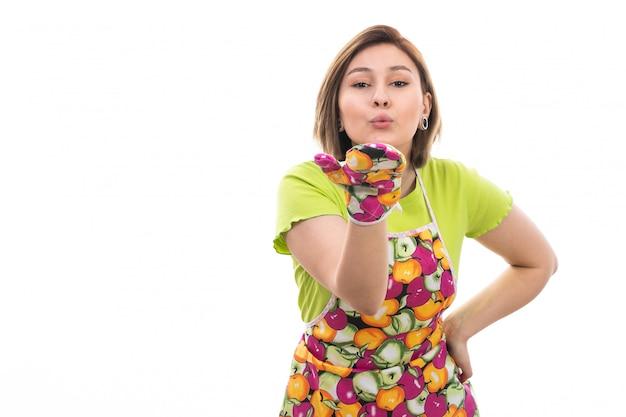 Eine junge schöne hausfrau der vorderansicht im bunten umhang des grünen hemdes, das luftküsse auf der hausreinigungsküche des weißen hintergrundhauses sendet