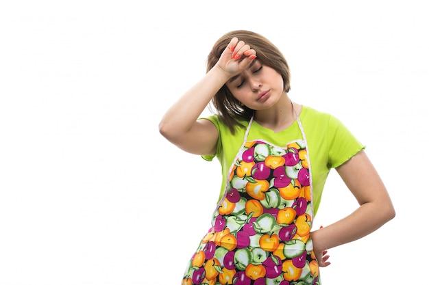 Eine junge schöne hausfrau der vorderansicht im bunten umhang des grünen hemdes, die erschöpften müden ausdruck auf der weiblichen küche des weißen hintergrundhauses aufwirft