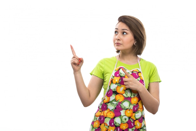 Eine junge schöne hausfrau der vorderansicht im bunten umhang des grünen hemdes, die überrascht aufwirft, zögerte, in den himmelausdruck auf der weiblichen küche des weißen hintergrundhauses zu schauen