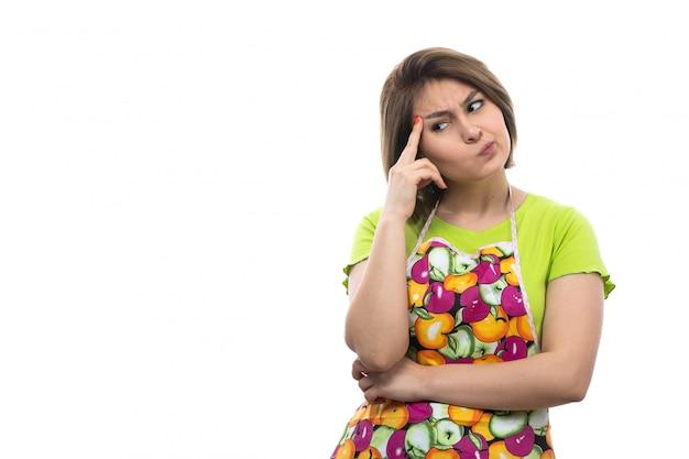 Eine junge schöne hausfrau der vorderansicht im bunten umhang des grünen hemdes zögerte