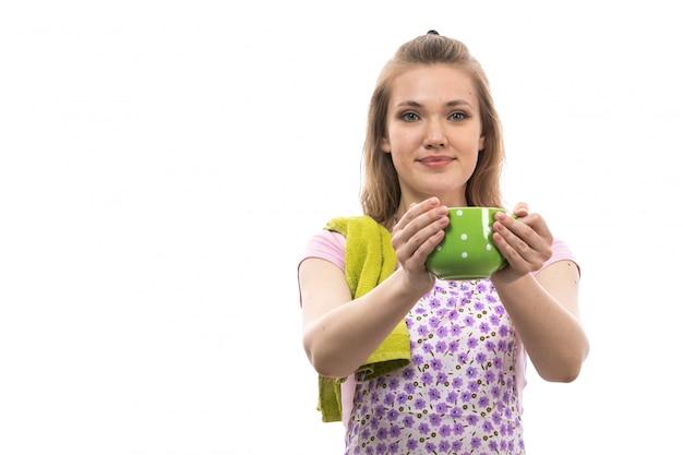 Eine junge schöne hausfrau der vorderansicht im bunten umhang des rosa hemdes, der die lächelnde aufstellung der grünen tasse hält