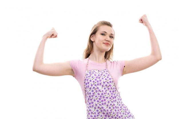 Eine junge schöne hausfrau der vorderansicht im bunten umhang des rosa hemdes glücklich lächelndes biegen