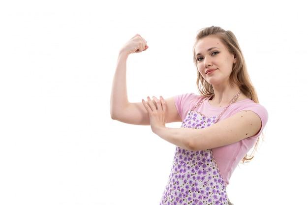Eine junge schöne hausfrau der vorderansicht im bunten umhang des rosa hemdes lächelnd biegend