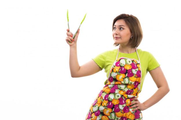 Eine junge schöne hausfrau der vorderansicht in buntem umhang des grünen hemdes, der grünes küchengerät hält, das auf der weißen hintergrundhausreinigungsküche lächelt
