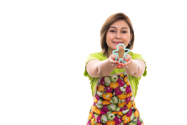 Eine junge schöne hausfrau der vorderansicht in buntem umhang des grünen hemdes, die blaue menschliche figurenform hält, die auf der hausreinigungsküche des weißen hintergrundhauses lächelt