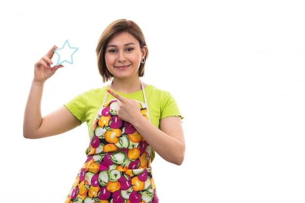Eine junge schöne hausfrau der vorderansicht in buntem umhang des grünen hemdes, die blaue stern geformte figur hält, die auf der hausreinigungsküche des weißen hintergrundhauses lächelt
