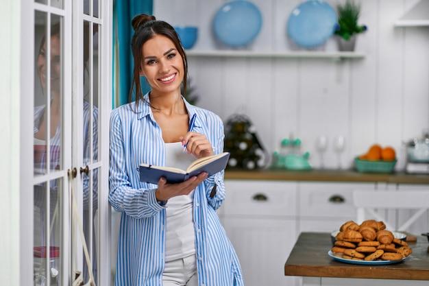 Eine junge schöne hausfrau steht mit einem notizbuch in der küche und schreibt ein kuchenrezept zum kochen auf.