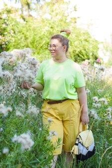 Eine junge schöne lächelnde frau in modischen flugshorts und einem t-shirt. positives modell plus größe im freien im feld. hält blumen in ihren händen. ein glückliches mädchen.