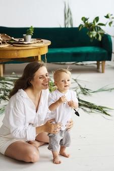Eine junge schöne mutter, die mit ihrem baby auf dem boden auf einem hintergrund von pflanzen und grünem sofa spielt