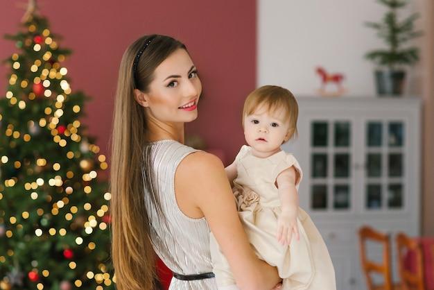 Eine junge schöne mutter hält ihre einjährige tochter in einem beigen kleid vor dem hintergrund von weihnachtsbäumen im wohnzimmer des hauses