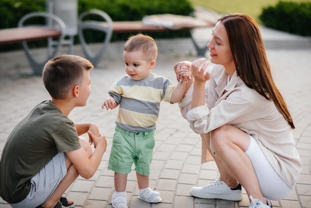 Eine junge schöne mutter mit zwei kleinen jungen spielt während des sonnenuntergangs im park. glücklicher familienspaziergang mit kindern im park. Premium Fotos