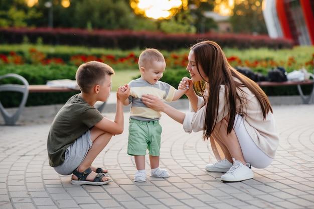 Eine junge schöne mutter mit zwei kleinen jungen spielt während des sonnenuntergangs im park. glücklicher familienspaziergang mit kindern im park.