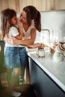 Eine junge schöne mutter und eine weinende tochter bereiten kakao in einer stilvollen wohnküche zu.
