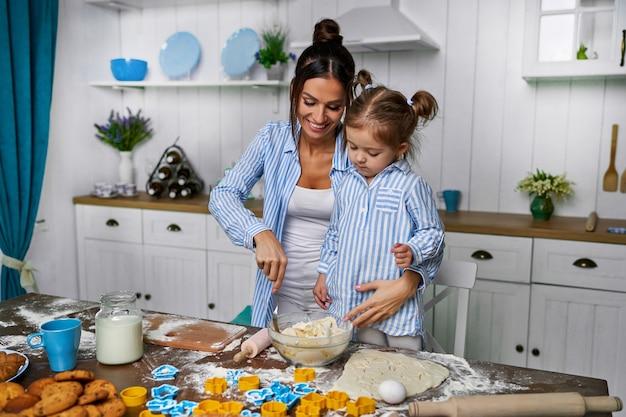 Eine junge schöne mutter und ihre süße tochter stehen in der küche am tisch