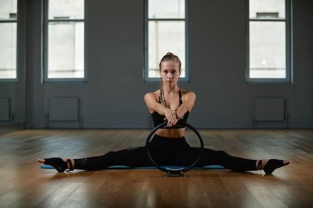 Eine junge, schöne, sportliche frau macht übungen mit einem pilates-ring im fitnessstudio. sport slawische frau in einem schwarzen anzug.