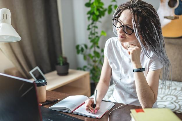 Eine junge schöne studentin mit dreadlocks lernt bei einer online-lektion zu hause auf einem laptop