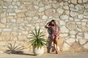 Eine junge schöne Frau in kurzem Kleid geht durch die Straßen einer europäischen Kleinstadt.