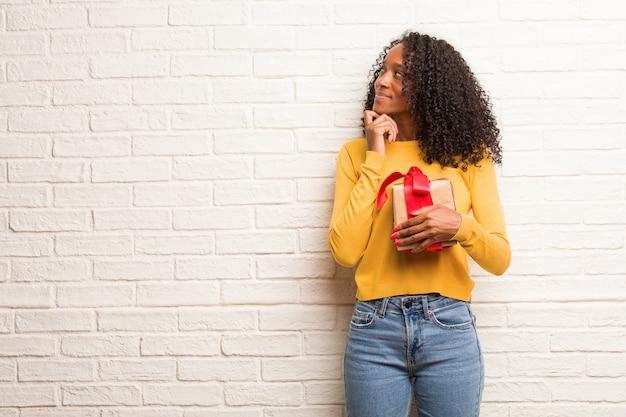 Eine junge schwarze frau, die über eine idee verwirrt und nachdenklich sucht, würde versuchen, eine lösung zu finden
