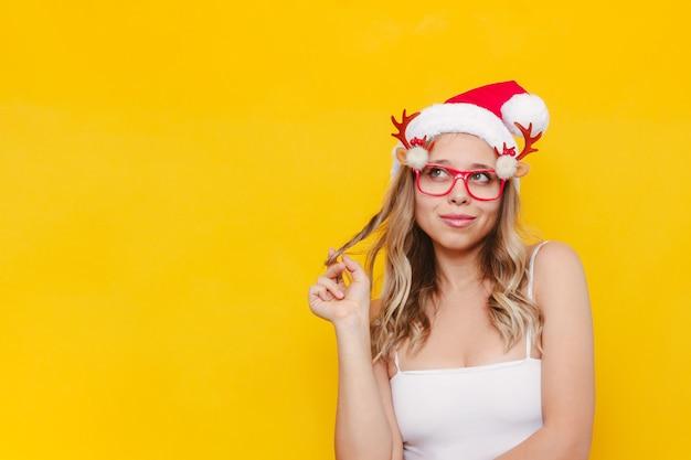 Eine junge sexy blonde frau in einer weihnachtsmütze, die wegschaut und eine haarlocke an ihrem finger dreht