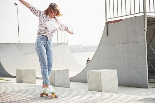 Eine junge sportfrau, die in einem park auf einem skateboard reitet.