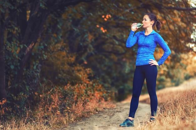 Eine junge sportliche joggerin in einer blauen sportjacke mit kapuze und schwarzen leggins trinkt nach dem joggen wasser aus der flasche
