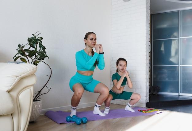 Eine junge sportliche mutter und ein mädchen machen zu hause gemeinsam übungen